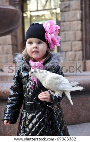 Cute little girl holding a white dove - stock photo