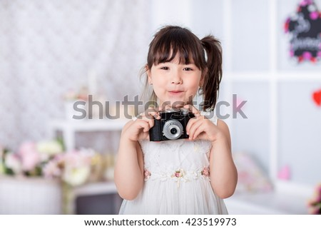 cute little girl holding an old camera. child taking pictures on an old camera - stock photo