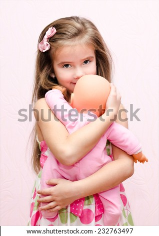 Cute little girl holding and embracing her doll isolated - stock photo