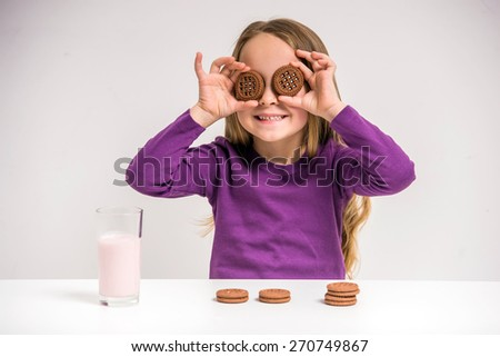 Cute little girl holding cookie while sitting at the table on grey background. - stock photo