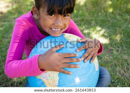 Cute little girl holding globe on a sunny day - stock photo