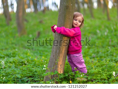 Cute little girl hugging a tree trunk in the spring forest - stock photo