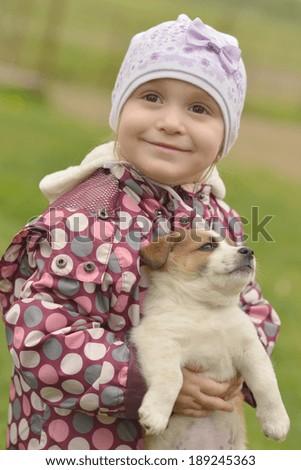 Cute little girl hugging dog puppy - stock photo