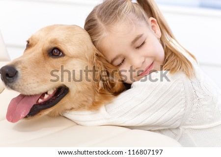 Cute little girl hugging golden retriever with love eyes closed, smiling. - stock photo