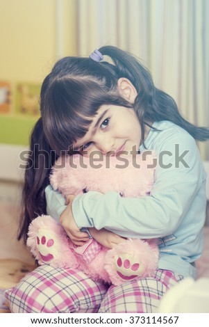 Cute little girl hugging her teddy bear in bed. Cross processed image with shallow depth of field - stock photo