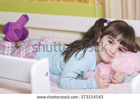 Cute little girl hugging her teddy bear in bed. Image with shallow depth of field - stock photo