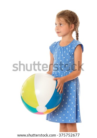 Cute little girl in a blue summer dress with polka dots holding hands on a beach ball . Closeup - Isolated on white background - stock photo
