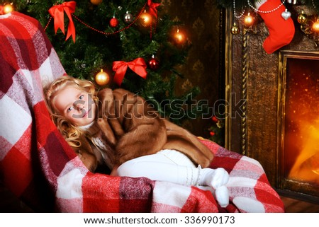 Cute little girl in a fur coat sitting in a room decorated for Christmas.  - stock photo