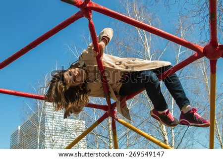 Cute little girl in a light coat and jeans climbed high on playground equipment on blue sky background in spring - stock photo