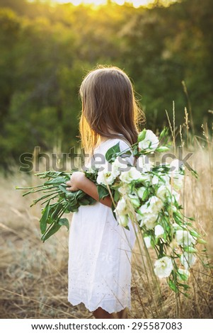 Cute little girl in a meadow with white wild summer flowers - stock photo