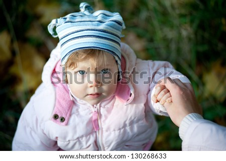 Cute little girl in a pink jacket and blue cap in autumn park / Cute little girl  in autumn park - stock photo
