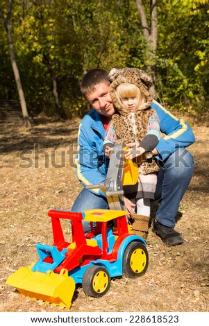 Cute little girl in a spotted cat suit posing in the arms of her kneeling father outdoors in q park with a large colorful plastic construction toy with a front end loader - stock photo