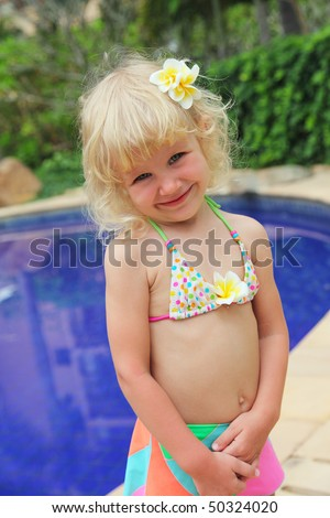 Cute little girl in a swimsuit at the pool - stock photo