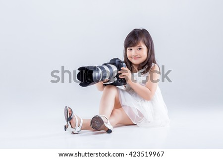 cute little girl in a white dress holding a big digital camera. child photographs - stock photo