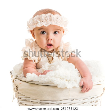 cute little girl in a wicker basket with lace headband - stock photo