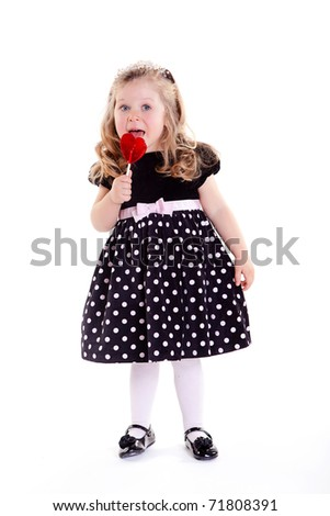 Cute little girl in beautiful dress with big heart lollypop - stock photo