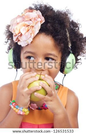 Cute little girl in big headphones biting an apple - stock photo