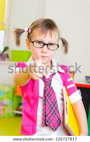 Cute little girl in glasses and pink necktie showing thumb up sign - stock photo