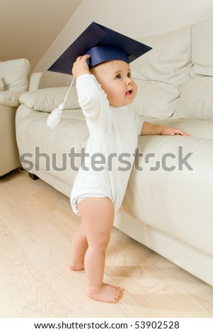 Cute little girl in graduation cap learning to walk - stock photo