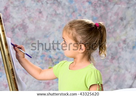 Cute little girl in green blouse playing with water colors on easel. - stock photo