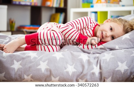 Cute little girl in pajama sleeping in bed - stock photo