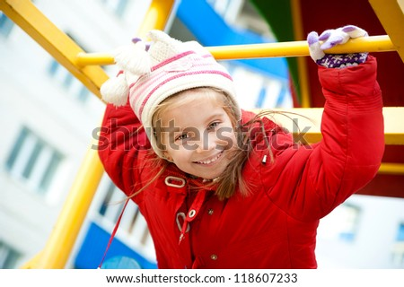 Cute little girl in red on outdoor playground equipment - stock photo