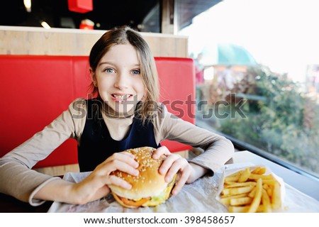 Cute little girl in school uniform eating a hamburger and potatos in the restaurant - stock photo