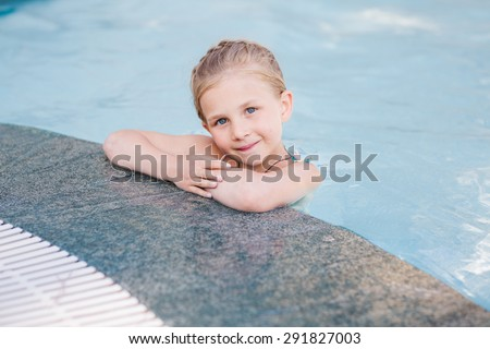 Cute little girl in swimming pool learning how to swim - stock photo