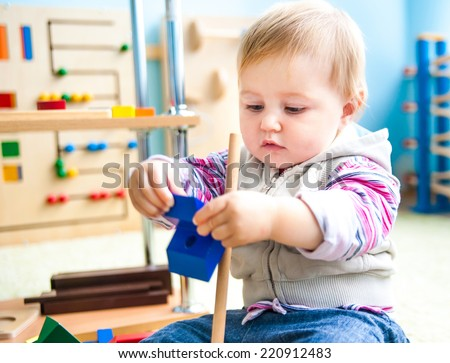 cute little girl in the classroom early development plays with numerous  toys - stock photo
