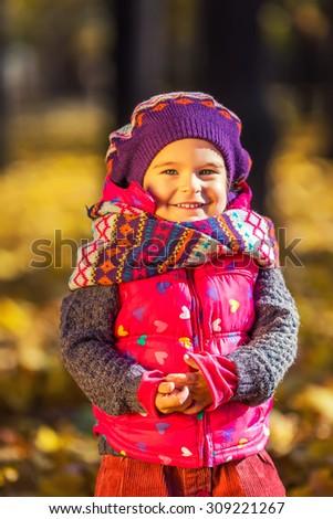 Cute little girl in the sunny autumn park - stock photo