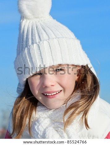 cute little girl in warm clothing outdoors lying on the snow - stock photo