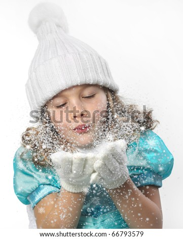 cute little girl in warm hat and gloves blowing snow on white background - stock photo
