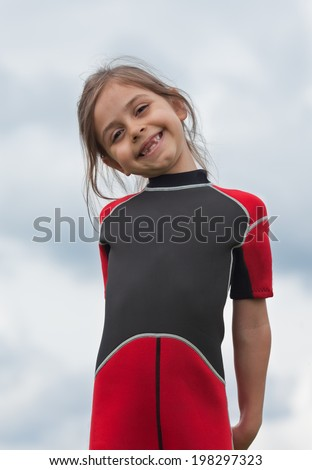 Cute little girl in wetsuit waiting for lesson windsurfing. Beautiful smile that is missing it's two front teeth - stock photo