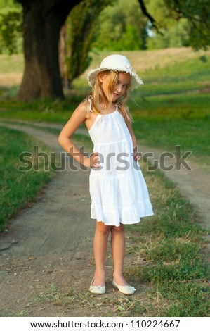 Cute little girl in white dress and hat standing on the country road on beautiful summer day. - stock photo