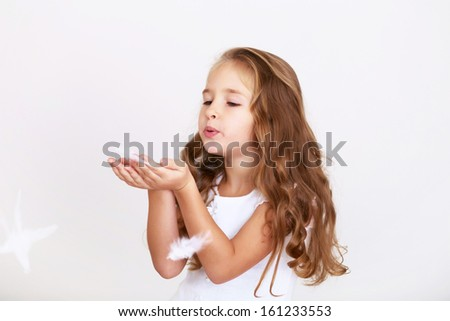 Cute little girl in white dress blowing on feathers on white background - stock photo