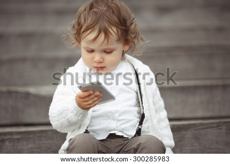 Cute little girl in white knitted sweater playing with mobile phone outdoors - stock photo