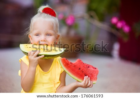 Cute little girl in yellow swimming suit eating red and yellow watermelon - stock photo