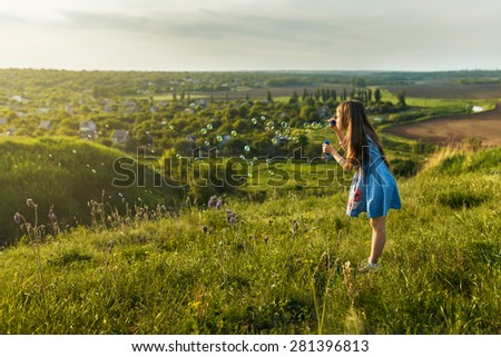 Cute little girl is blowing a soap bubbles on the mountain - stock photo