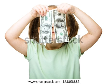 Cute little girl is covering her eyes with dollars, isolated over white - stock photo