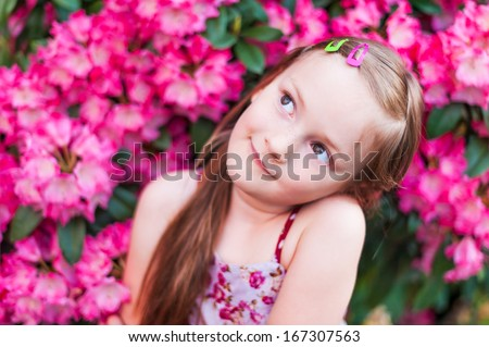 Cute little girl is daydreaming in pink flowers - stock photo