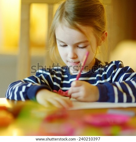 Cute little girl is drawing with pencils in preschool - stock photo