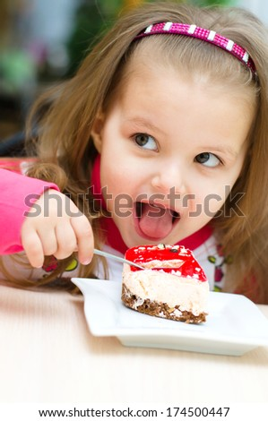 Cute little girl is eating cake in parlor - stock photo