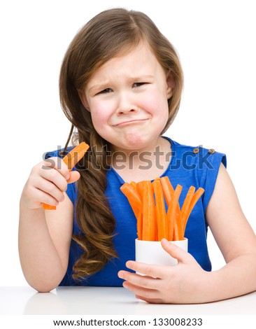 Cute little girl is eating carrot and feel very unhappy about it, isolated over white - stock photo