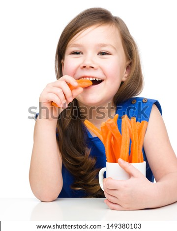 Cute little girl is eating carrot, isolated over white - stock photo