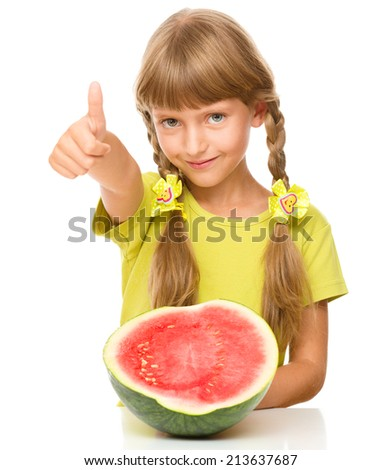 Cute little girl is eating watermelon and showing thumb up sign, isolated over white - stock photo