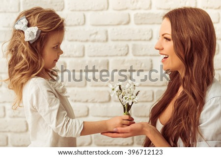 Cute little girl is giving flowers to her beautiful young mother, against white brick wall - stock photo