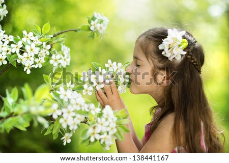 Cute little girl is holding flower outside in the green park - stock photo