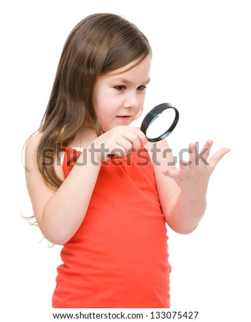 Cute little girl is looking at her palm through magnifier, isolated over white - stock photo