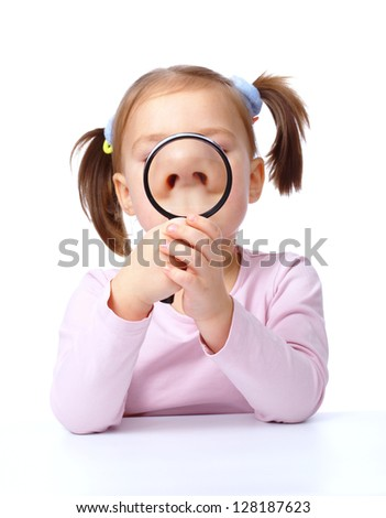 Cute little girl is looking through magnifier, isolated over white - stock photo