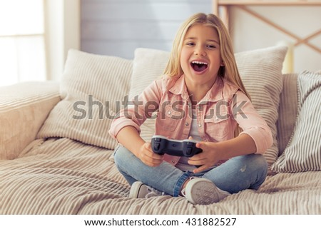 Cute little girl is playing game console and smiling while sitting on the sofa at home - stock photo